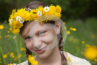 Girl with flowers on her head on a meadow in nature