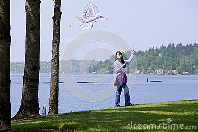 Girl flying kite by the lake