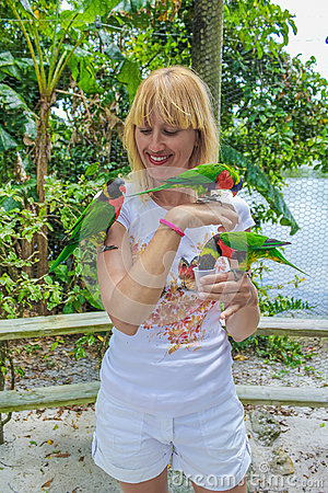 Woman feeding three parrots