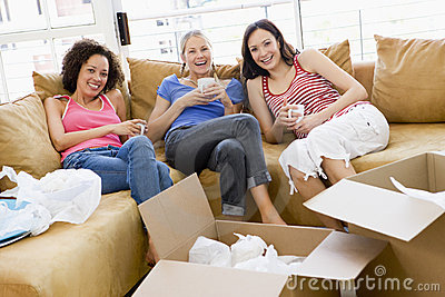 Girl friends with coffee by boxes in new home