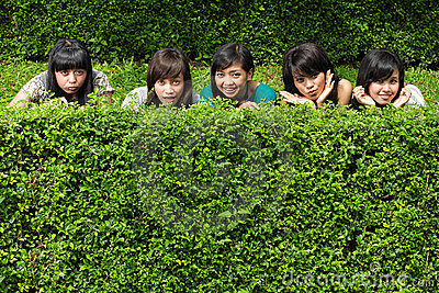 Girl friends group hiding behind the tree
