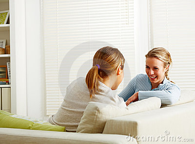 Girl friends talking together at home