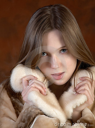The girl in a fur coat on motley background