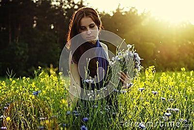 Girl gathering flowers on sunset