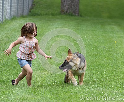 Girl with German Shepherd Dog puppy at park
