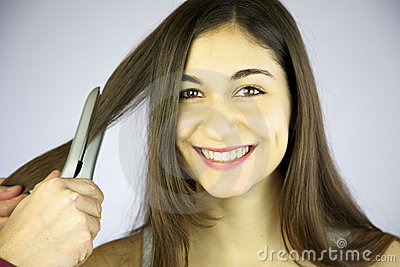 Girl gets her hair ironed smiling