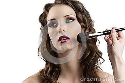 Girl getting made-up by hands with brushes