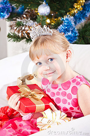 Girl with gifts near a New Year tree
