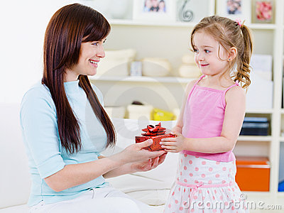 ... beautiful pretty girl giving a gift to her happy mother - indoors