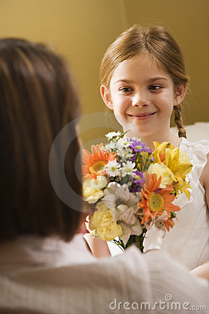 Girl giving mom flowers.