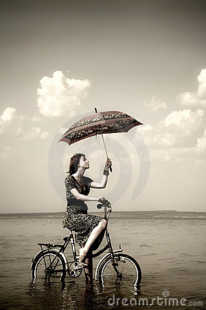 Girl go for a cycle ride at water with umbrella