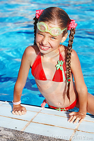 Girl with goggles, red swimsuit in swimming pool
