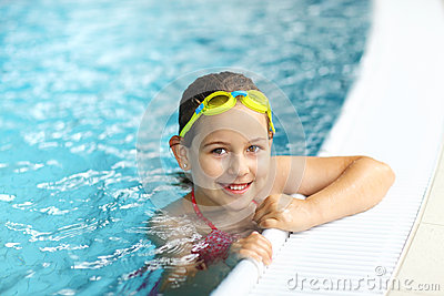 Girl with goggles in swimming pool