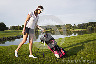 Girl golf player with golf bag.