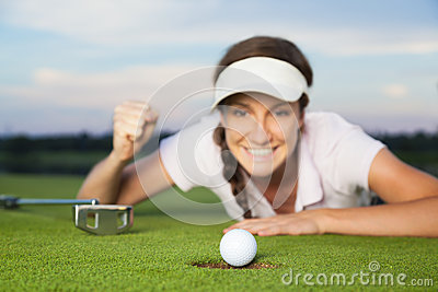 Girl golfer looking at ball dropping into cup.