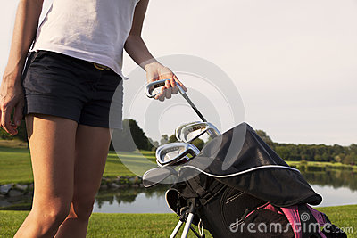 Girl golfer taking out iron from golf bag.