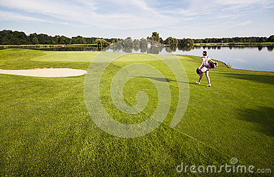 Girl golfer walking on golf course with golf bag.