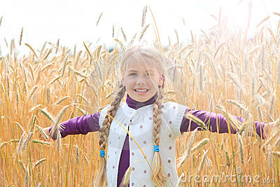 Girl in grainfield arms wide open smiling