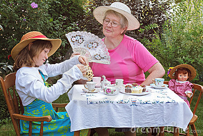 Girl and grandmother have a tea party