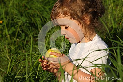 Girl in grass with green apple