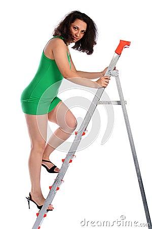 Girl in green dress going up on ladder.