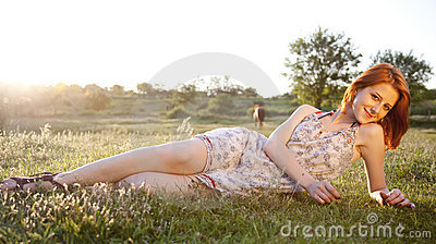 Girl at green grass field at sunset.