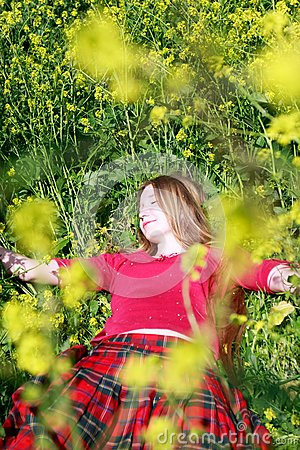 Girl in green grass and yellow flowers