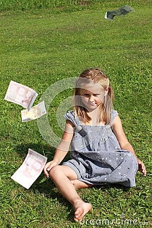 Girl in grey dress sitting watching flying money