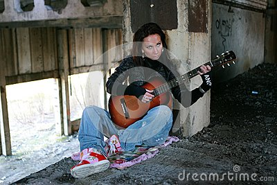 Girl with a guitar in a deserted factory