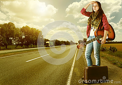 Girl with guitare and suitcase on highway