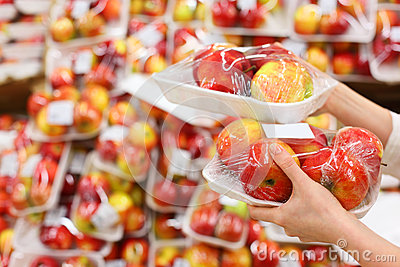 Girl hands hold packed apples in store