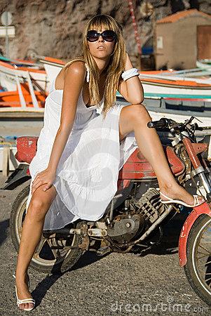 A girl in the harbor with a motocycle