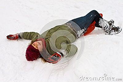 Girl has fun lying in the snow
