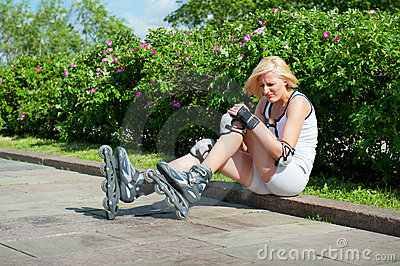 Girl has hit a knee skating on roller-skaters Stock Photo