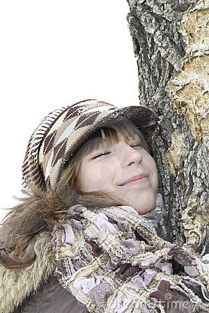 The girl has nestled a cheek on a tree trunk
