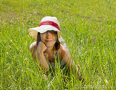 Girl in hat lying at meadow