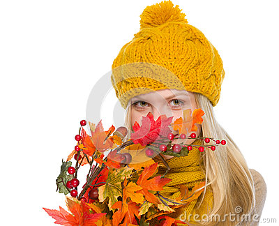 Girl in hat and scarf hiding behind autumn bouquet