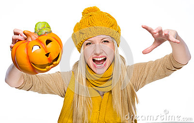 Girl in hat and scarf scaring with jack-o-lantern