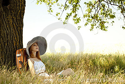 Girl in hat sitting near tree at countryside.