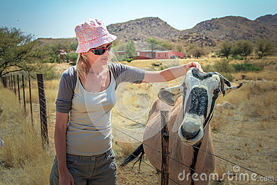 Girl with hat touches gemsbok