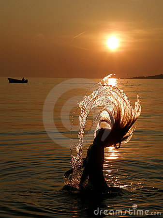 Girl have a fun in sea at sunset