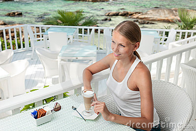 Girl having coffee break in an ocean view cafe
