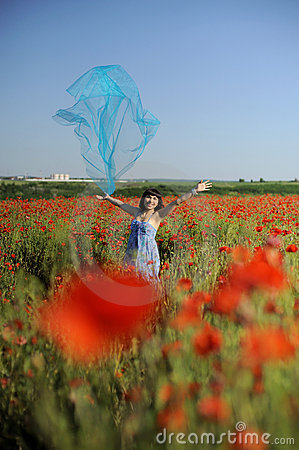 Girl having fun in poppies with blue cloth