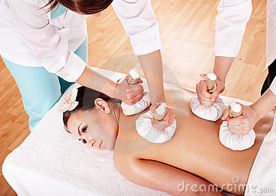 Girl having Thai herb compress massage.