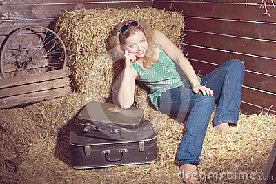Girl in hay near the luggage
