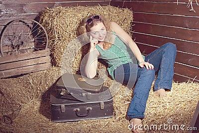 Girl in hay near the luggage