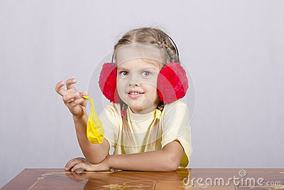 Girl with headphones and a ball is sitting at table