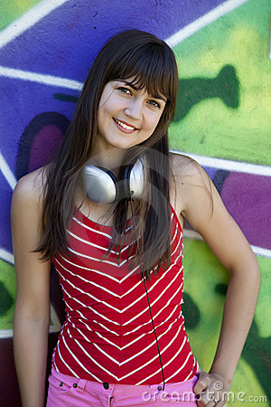Girl with headphones and graffiti wall