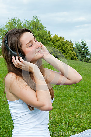 Girl in headphones listens to music in the park.