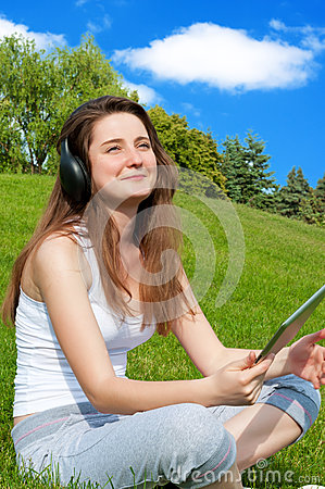 Girl with headphones and a tablet in the park.